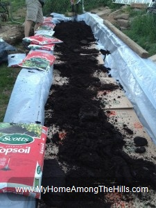 Lining the raised bed garden with plastic and cardboard